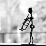 metal stick figure playing the trumpet